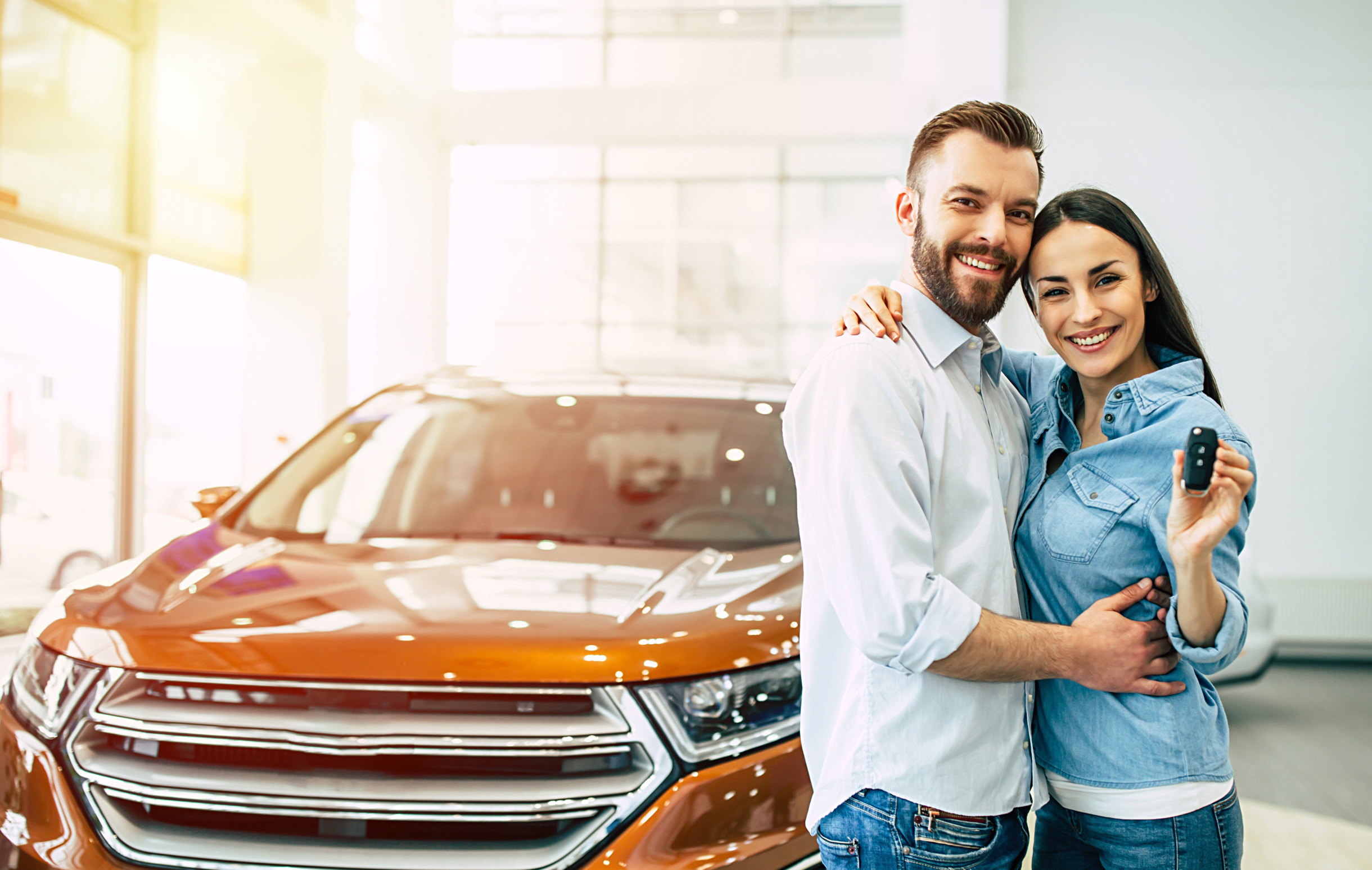 Couple holding keys and with new car